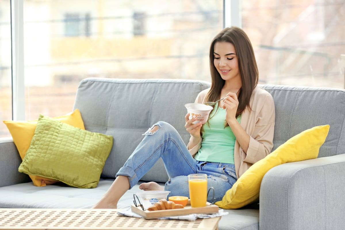 Una chica comiendo yogur sentada en un sofá